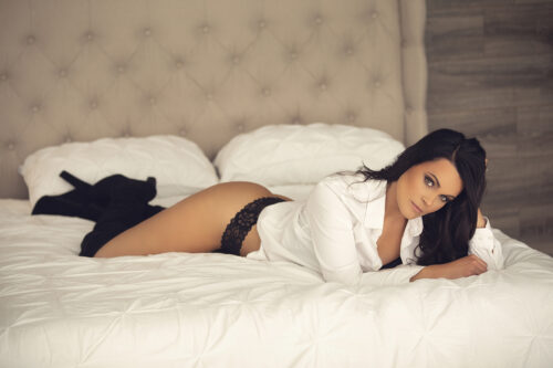 what to wear//comfy boudoir photo//white button down with lazy black panty//Black high heel boots//Laying on bed boudoir pose// See more at boudoirbytracylynn.com