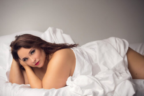 Boudoir myths busted// implied nude photo in white sheets and natural light.