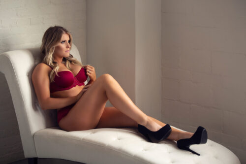 Boudoir gifts for Christmas. Model is wearing a red bra and panty set with black high heels. She is sitting on a cream chaise lounge. See more at boudoirbytracylynn.com